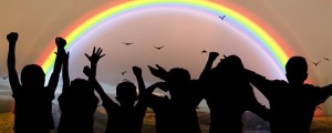 Children in silhouette under a rainbow.