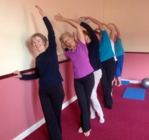 Five ladies carrying out a stretching exercise at a Stott Pilates lesson.