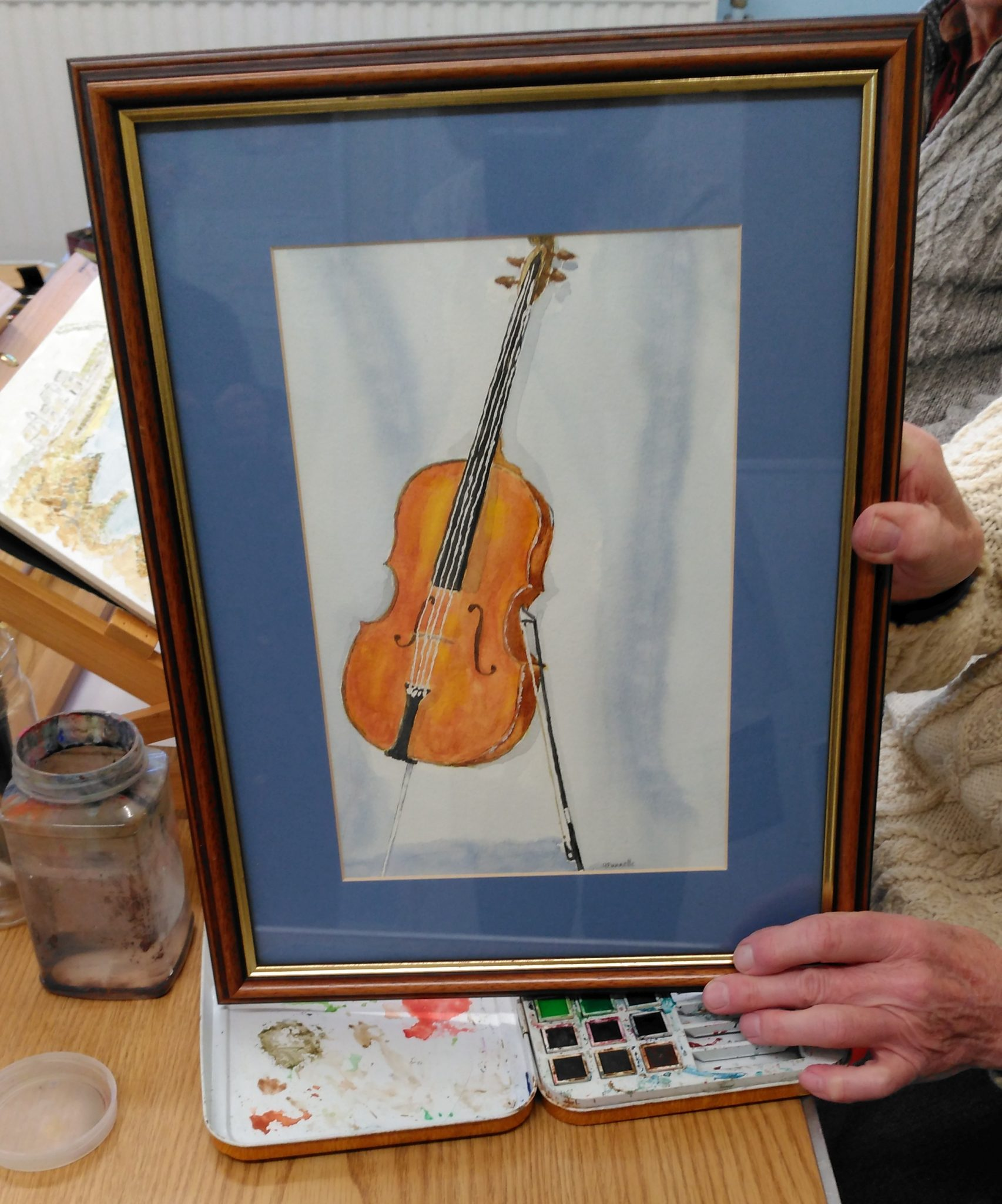 A framed watercolour paining of a cello being held by the artist.