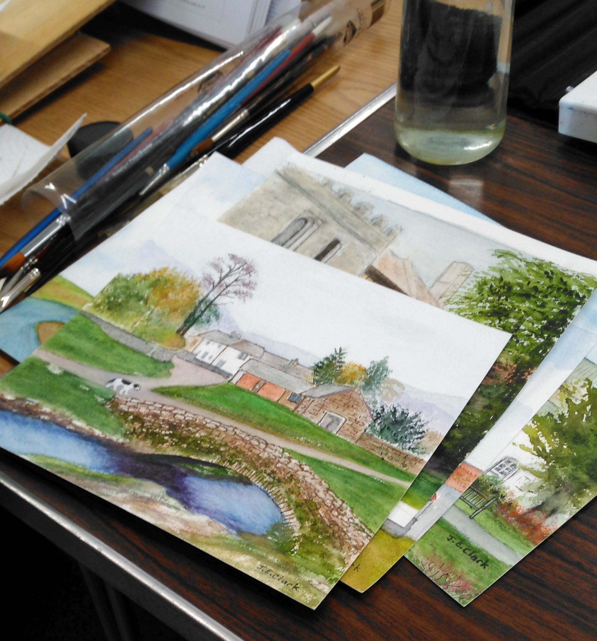 A pile of watercolours on a table with brushes and a water pot.