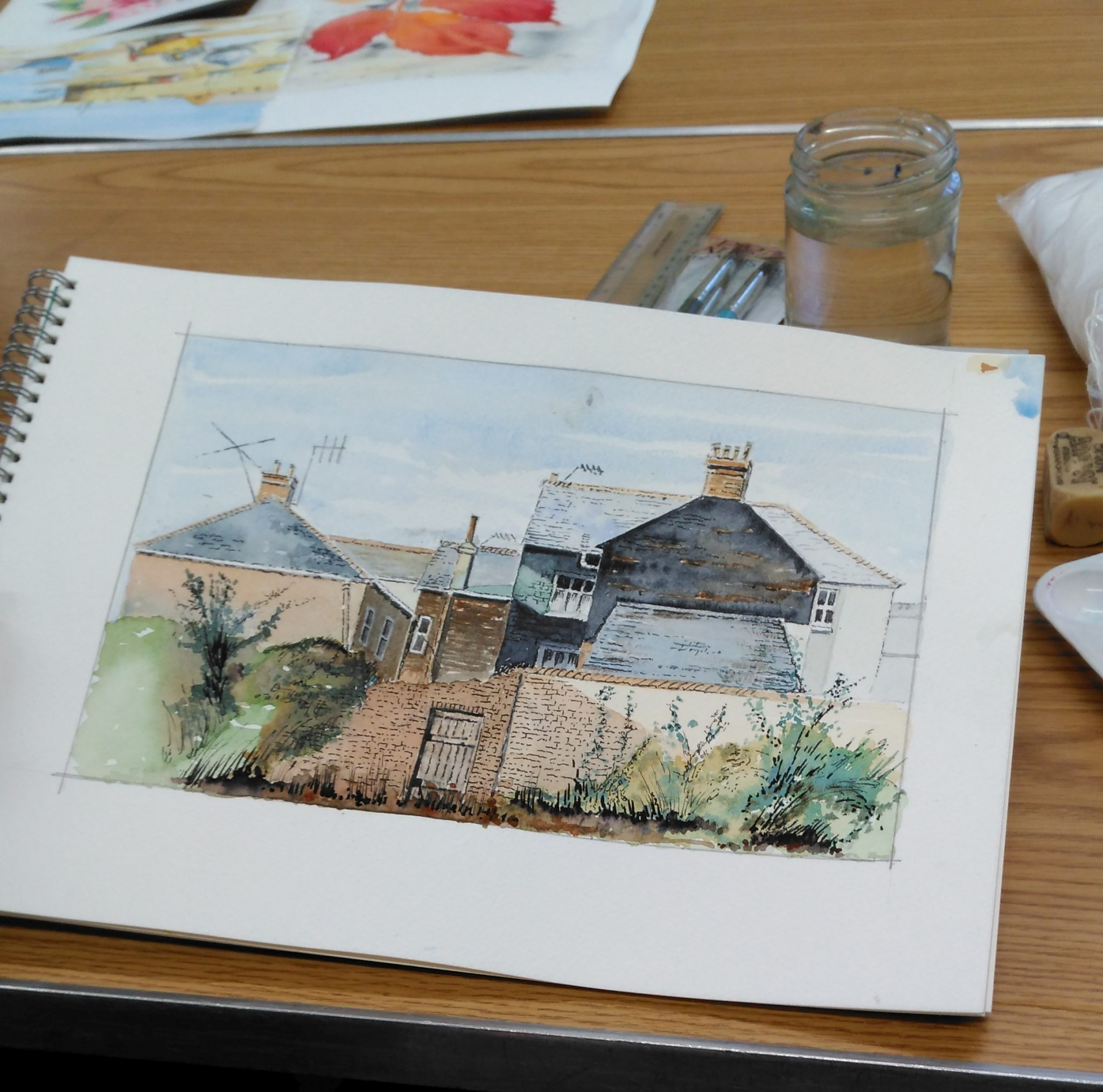 A sketch pad open to a page with a painting of terraced houses.