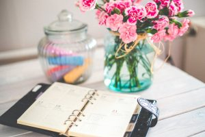 A diary on a desk next to a vase of flowers and a jar of coloured crayons