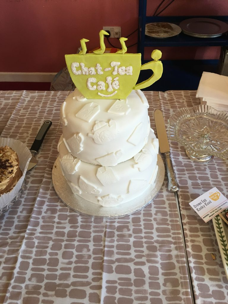 Picture of white iced cake with Chat-Tea Cafe Logo in green icing on top.