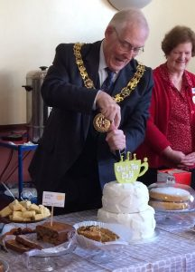 The mayor of Winchester cutting a cake at the Chat-Tea Café