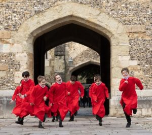 Winchester College Quiristers in red robes running through gothic arch