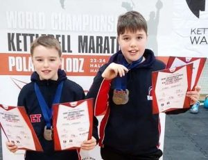 Boys showing their kettlebell competition certificates and medals