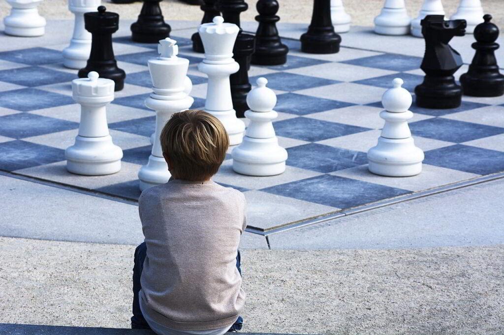 Boy sitting beside a giant chess board