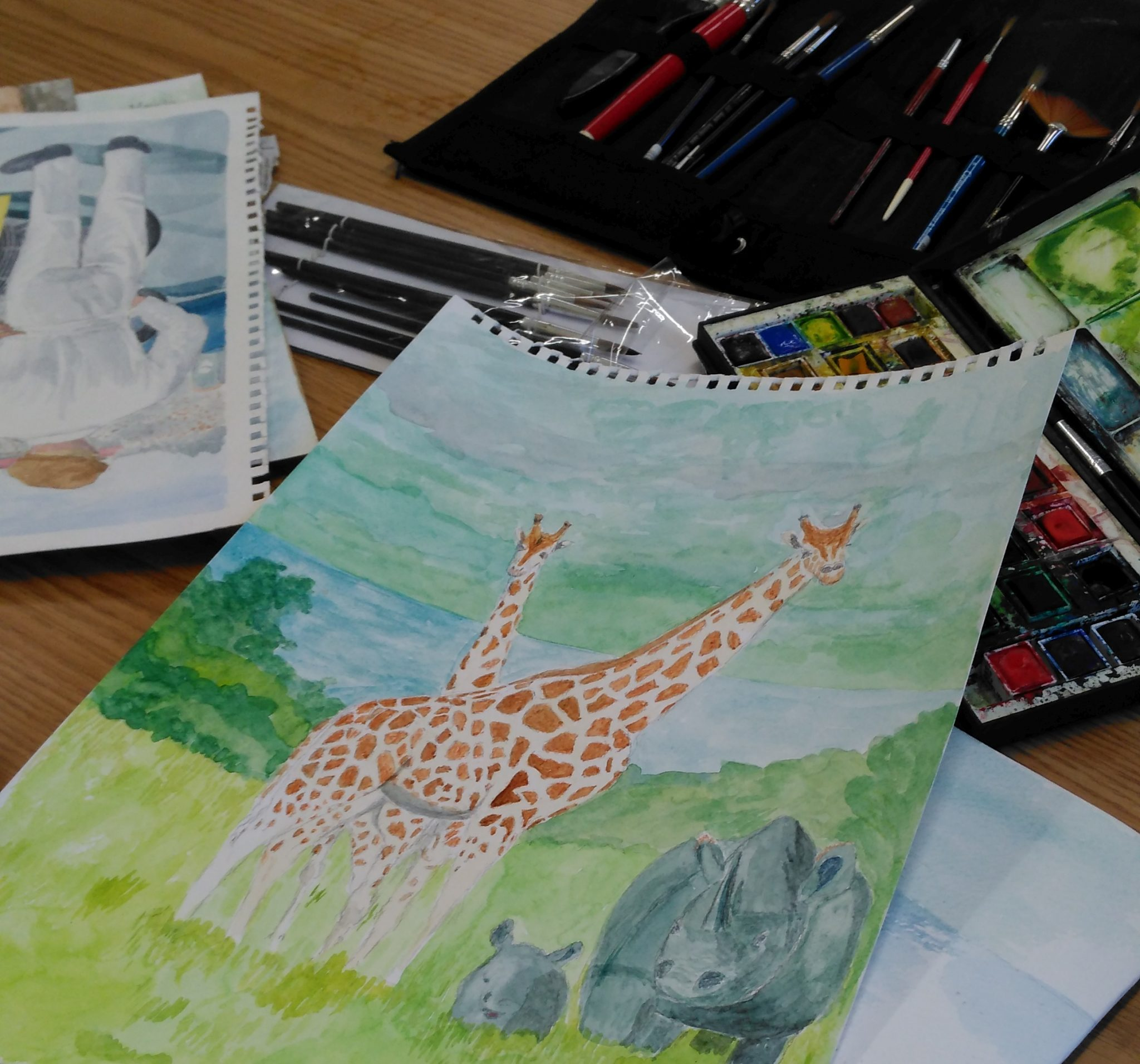 A few watercolour paintings, with a paintbox and brushes.