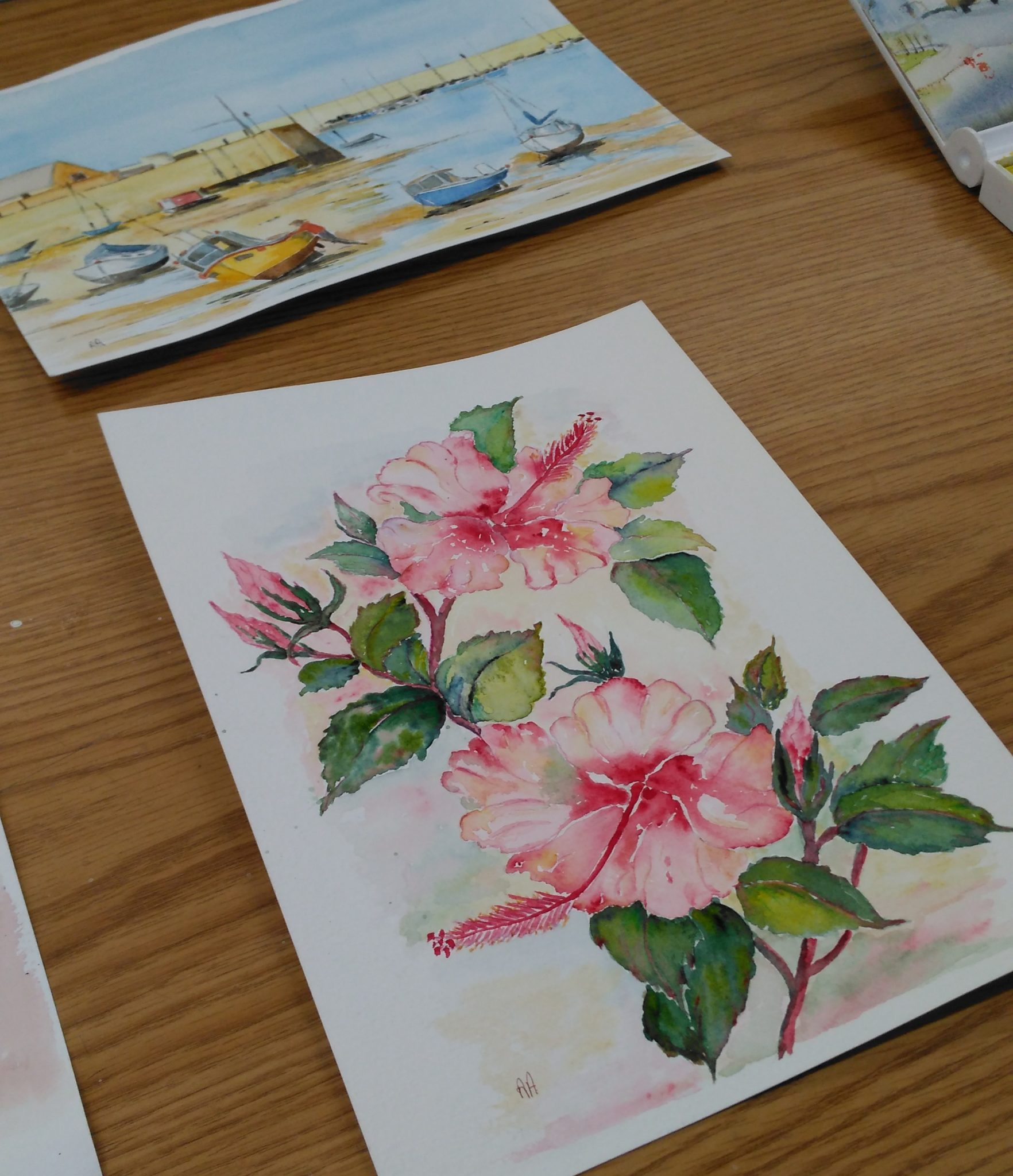 Two watercolours, one of pink flowers and one of a harbour with the tide out.