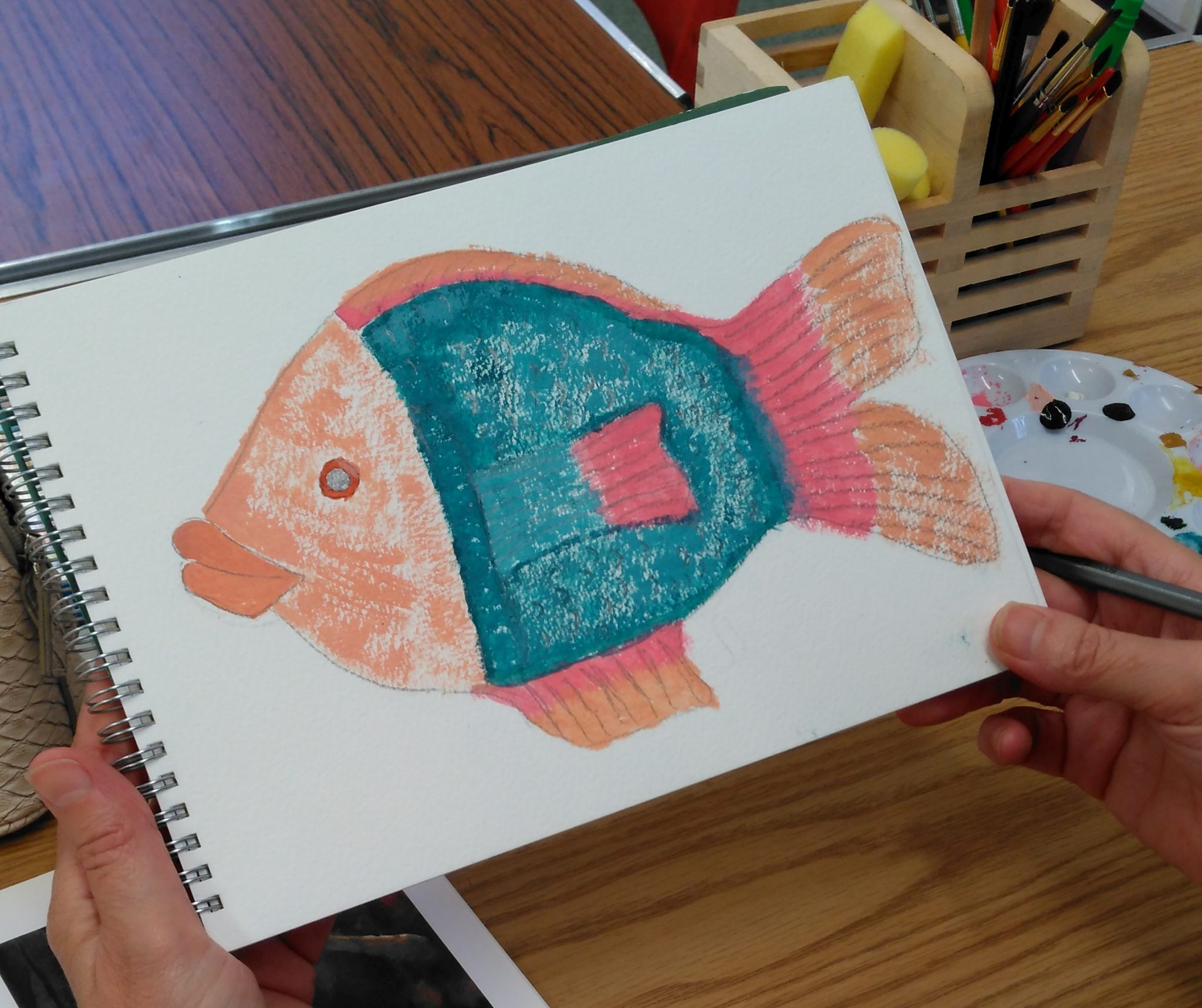 A sketchpad opened to a page with a painting of a fish.