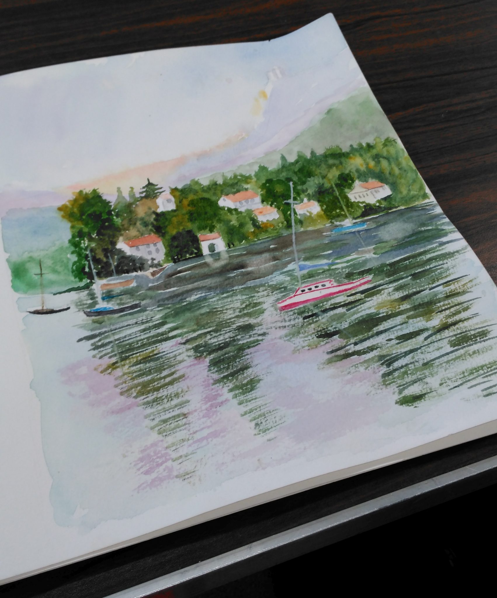 A sketchpad opened to a scene of boats on a lake.